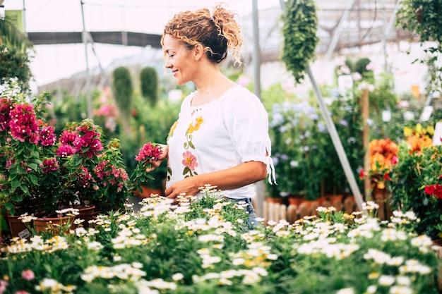A jovem em uma estufa com muitas mudas admira o crescimento de flores brancas como margaridas. conceito de cuidado e paixão pela natureza. compras e negócios relacionados à natureza e vida fácil das pessoas