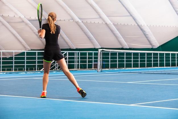 A jovem em uma quadra de tênis fechada com bola e raquete