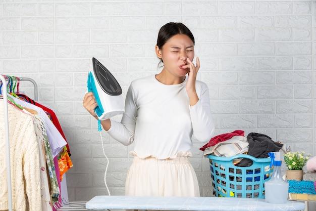 A jovem empregada que está chupando o dedo por causa do calor do ferro em um tijolo branco.