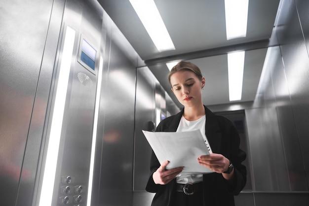 A jovem empresária está concentrada em ler a documentação no elevador.