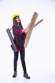 A jovem engenheira com capacete de segurança amarelo, abrindo a planta na mão, para verificar