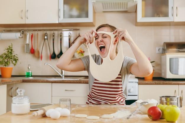 A jovem engraçada, alegre e sorridente coloca uma massa com buracos no rosto e se diverte na cozinha. cozinhando em casa. preparar comida.