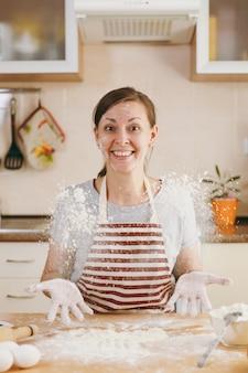 A jovem engraçada alegre sentada à mesa com farinha e vai preparar um bolo na cozinha. cozinhando em casa. preparar comida.