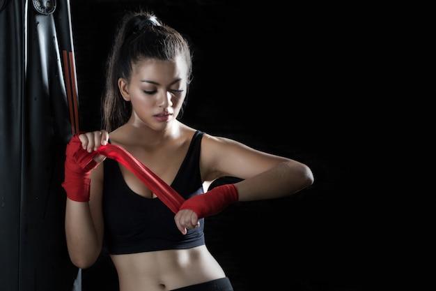 A jovem está de pé, envolta em um pano nas mãos para praticar boxe no ginásio.