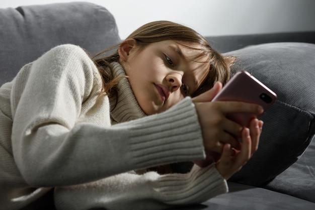 A jovem está olhando para a tela de um smartphone encostado na almofada do sofá.
