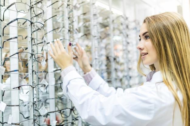 A jovem está se preparando para os estudos na faculdade e experimente os óculos da moda para seu visual perfeito em uma loja profissional
