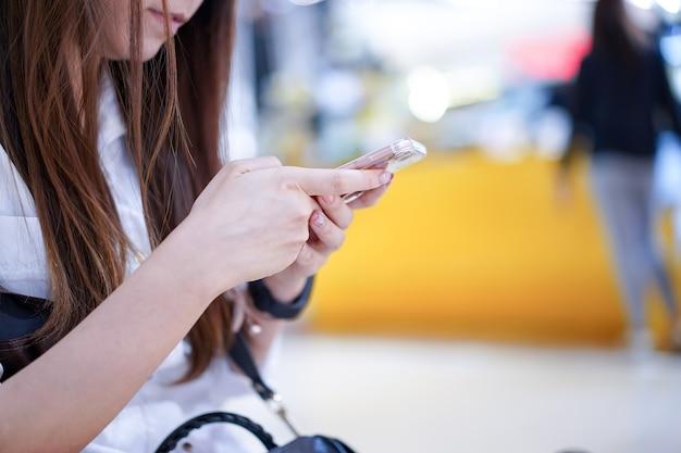 A jovem está segurando o telefone inteligente na mão (ao lado do ângulo / visão); brincando, digitando, conversando, enviando e-mail com a loja de departamentos bokeh embaçada atrás.