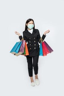 A jovem estava vestida de escuro com uma máscara e carregava uma sacola para fazer compras