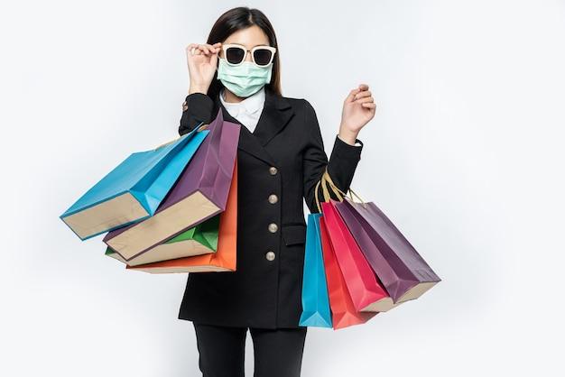 A jovem estava vestida de escuro, uma máscara e óculos e bolsas para ir às compras
