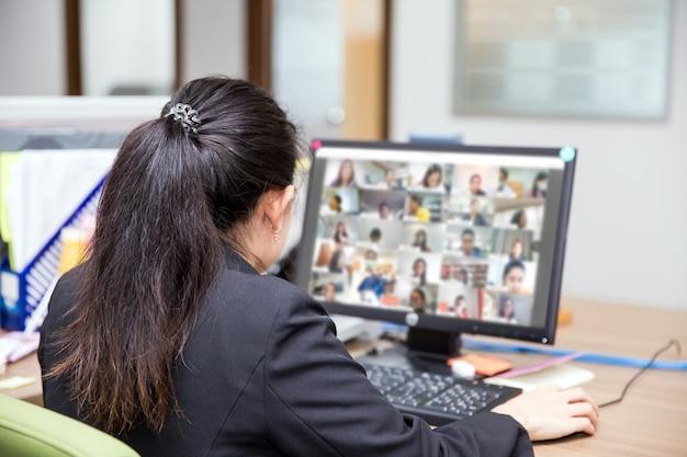 A jovem estudante usa o computador para aprender online com o programa de videochamada.