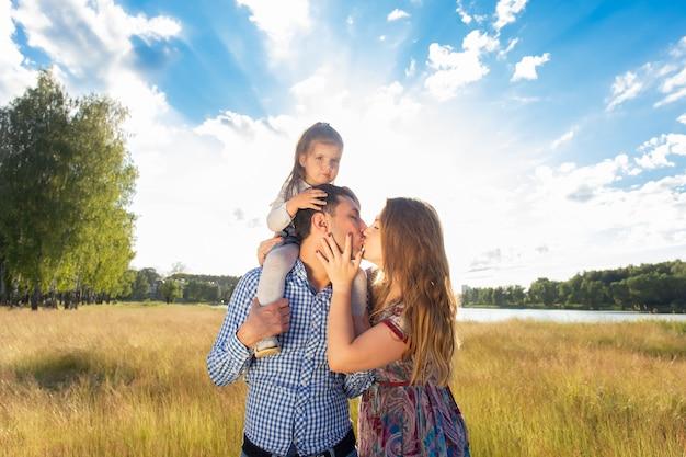 A jovem família feliz caminha na natureza, ao pôr do sol