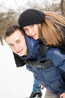 A jovem família joga madeira de inverno na neve