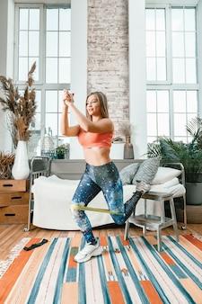 A jovem fazendo um treino com elástico de fitness esportivo para praticar esportes em casa