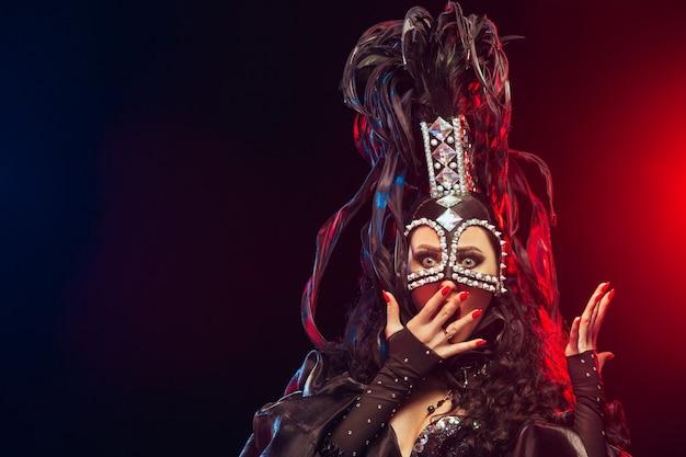 A jovem feliz sorridente linda dançarina feminina com vestidos de carnaval posando em fundo preto do estúdio