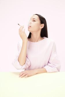 A jovem fumando cigarro enquanto está sentado à mesa no estúdio. cores da moda. o retrato de uma menina caucasiana em estilo minimalista com espaço de cópia