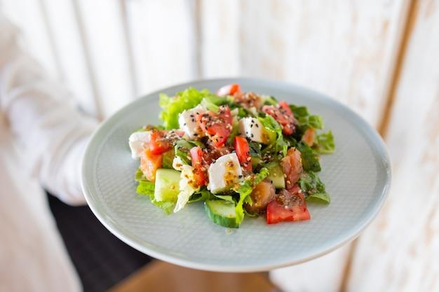 A jovem garçonete segurando nas mãos o prato com a salada grega.
