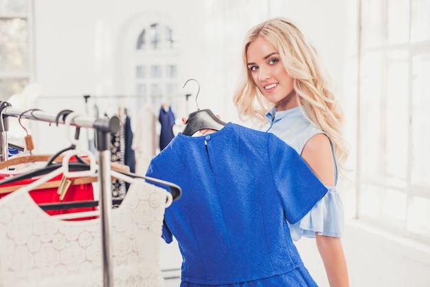 A jovem garota bonita escolhendo e experimentando vestidos na loja