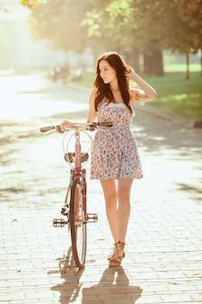 A jovem garota com bicicleta no parque