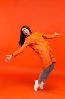 A jovem garota posando no estúdio outono casaco isolado no vermelho. emoções negativas humanas.