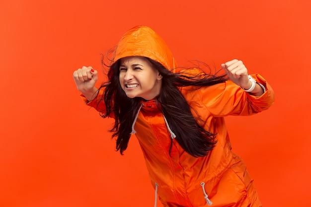 A jovem garota posando no estúdio outono casaco isolado no vermelho.