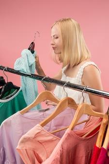 A jovem infeliz olhando vestidos e experimentando enquanto escolhe na loja