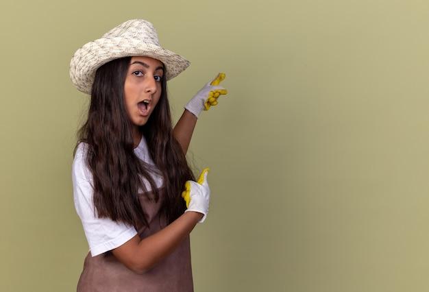 A jovem jardineira com avental e chapéu de verão usando luvas de trabalho surpreendida apontando com o dedo indicador para o lado em pé sobre a parede verde