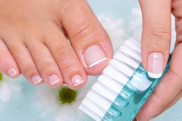 A jovem lava e limpa as unhas dos pés com água usando uma escova de limpeza