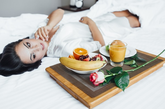 A jovem linda morena feliz deita-se em sua cama pela manhã, ao lado de croissant, suco de laranja e romã de banana na bandeja e rosa