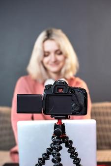 A jovem loira criadora de conteúdo está em seu laptop na mesa