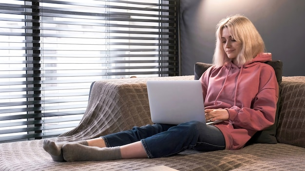 A jovem loira criadora de conteúdo está em seu laptop, sentada no sofá perto da janela