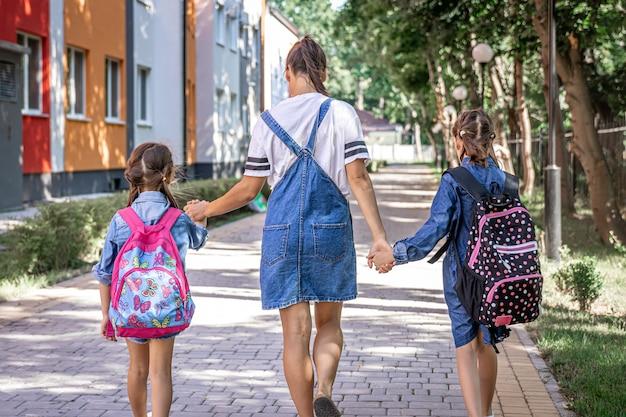 A jovem mãe acompanha as meninas à escola, vista traseira.