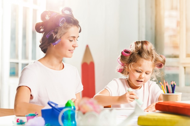 A jovem mãe e a filha pequena desenhando a lápis em casa