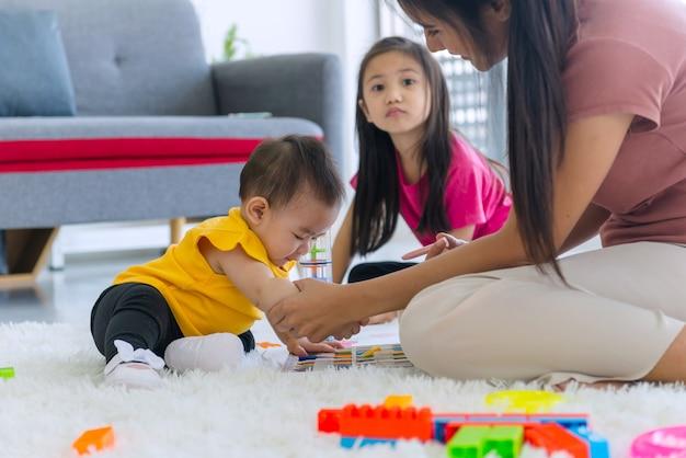 A jovem mãe e filha e a filha mais velha brincando na sala