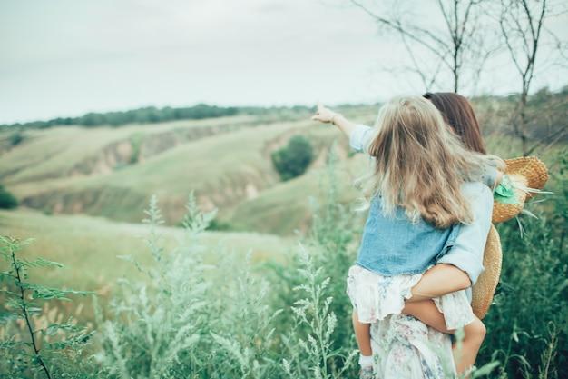 A jovem mãe e filha em fundo verde grama