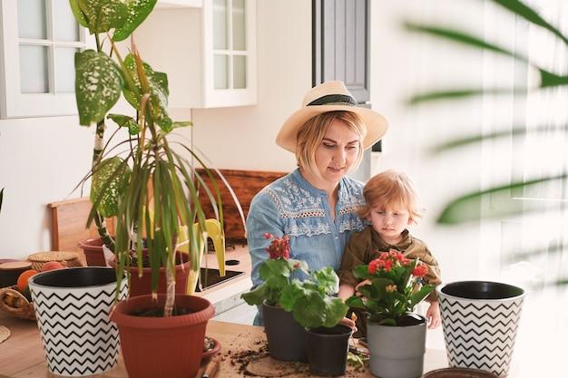 A jovem mãe e seu filho estão envolvidos no cultivo de flores caseiras em casa