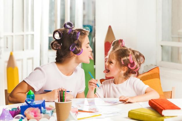 A jovem mãe e sua filha pequena desenhando com lápis em casa