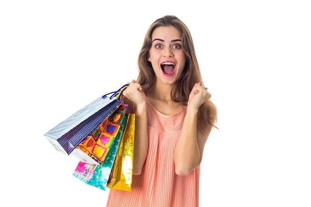 A jovem mantém os pacotes na mão e se alegra, closeup