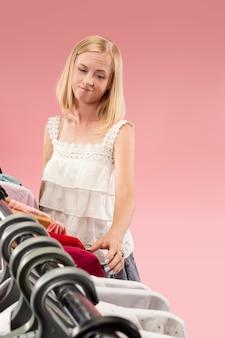 A jovem menina bonita infeliz olhando vestidos e experimentá-lo ao escolher na loja