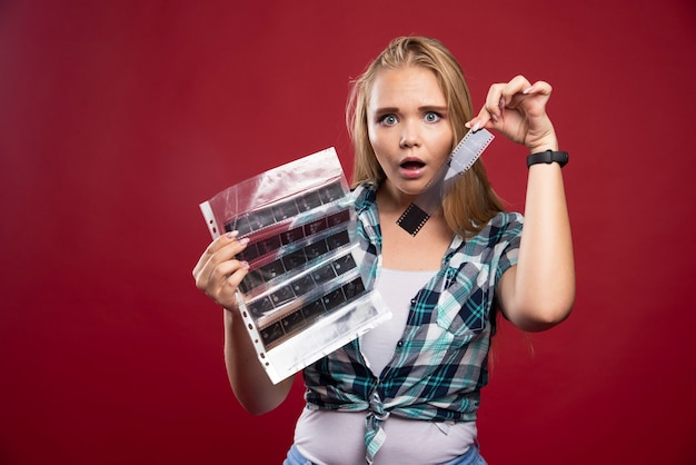 A jovem modelo loira verifica as cenas do filme polaroid e parece surpresa e desapontada.
