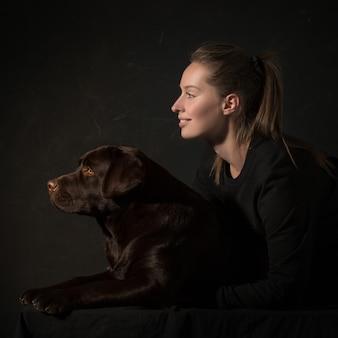 A jovem mulher abraçando um cão de raça misturada