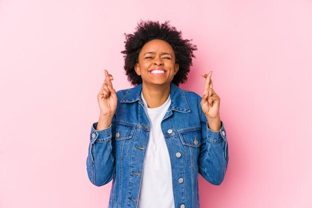 A jovem mulher afro-americana contra um fundo rosa isolou os dedos de cruzamento por ter sorte