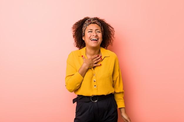 A jovem mulher afro-americana contra um rosa ri alto mantendo a mão no peito.