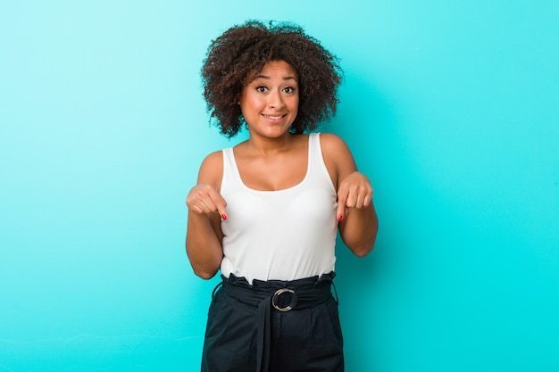 A jovem mulher afro-americano aponta para baixo com os dedos, sentimento positivo.