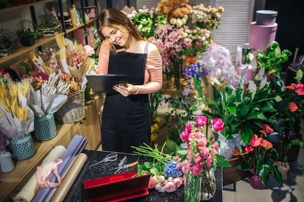 A jovem mulher alegre fala no telefone e olha o plahcnette preto. ela tem rolos de papel, latop vermelho e buquê de flores em tabe. florista é cercada por plantas.