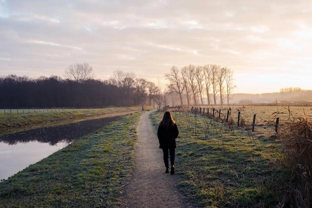 A jovem mulher anda em um dia frio pelo rio no por do sol, fundo bonito da paisagem colorido