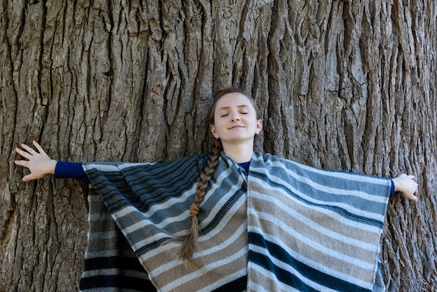 A jovem mulher apoiou as costas no tronco de uma grande árvore. olhos fechados. unidade com a natureza