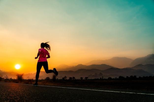 A jovem mulher aprecia correr fora com noite bonita do verão no campo.