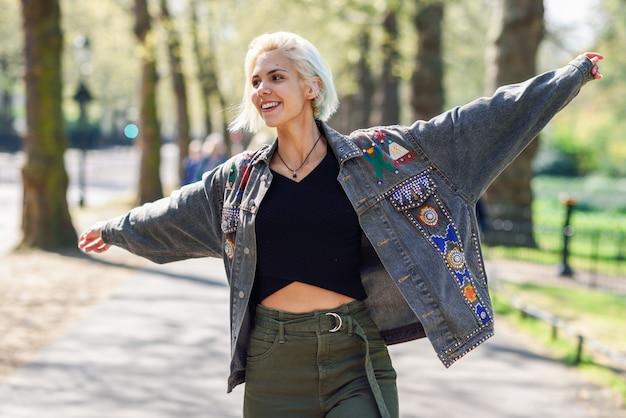 A jovem mulher arma-se aumentado apreciando o ar fresco no parque urbano verde.
