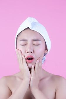 A jovem mulher ásia com pele fresca limpa toca em possuir a cara, expressões faciais expressivos, cosmetologia e termas.