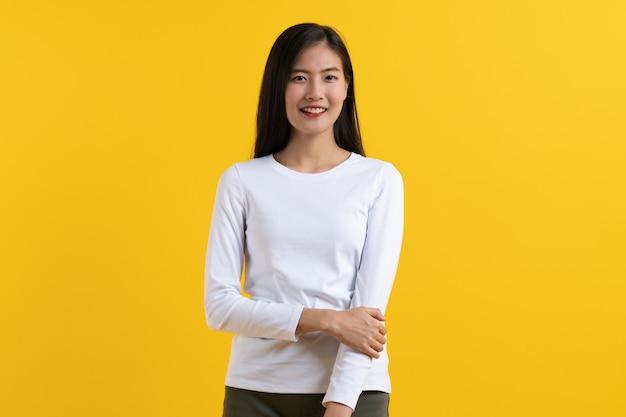 A jovem mulher asiática bonito no olhar ocasional da camisa branca que levanta a confiança dobrou os braços isolados no fundo amarelo no estúdio.